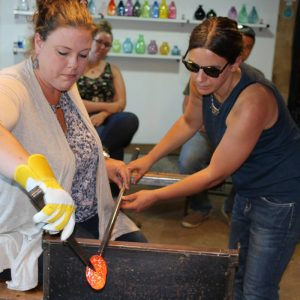 Woman Blowing Glass with Instructor