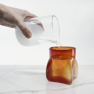 Hand Pouring Water Into A Colourful Handblown Glass Square Cup